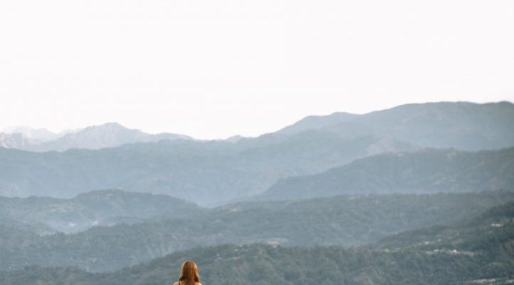 woman standing on cliff during daytime